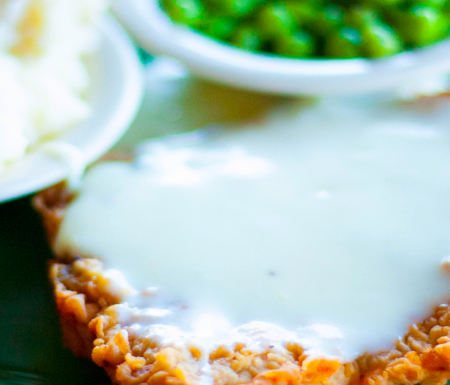 country fried steak, gravy, mashed potatoes, peas